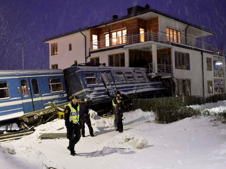 Police officers stand around a local train that derailed and crashed into a residential building in Saltsjobaden outside Stockholm