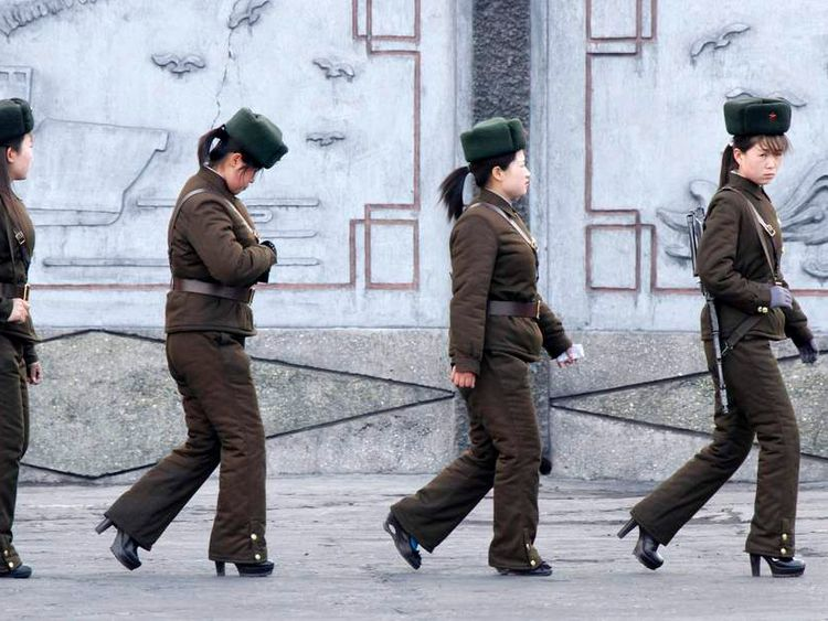 Female North Korean soldiers patrol along the banks of Yalu River, near the North Korean town of Sinuiju