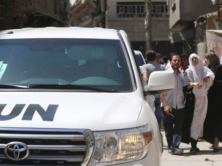 A woman affected by what activists said was an apparent gas attack is lead to a team of U.N. chemical weapons experts for checking during the team's visit to one of the sites of an alleged chemical weapons attack in the Damascus