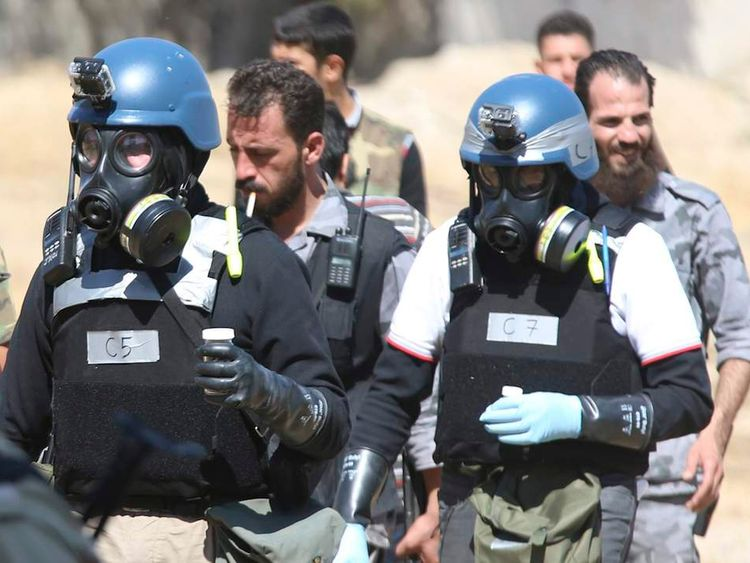 U.N. chemical weapons experts wearing gas masks carry samples from one of the sites of an alleged chemical weapons attack in the Ain Tarma neighbourhood of Damascus