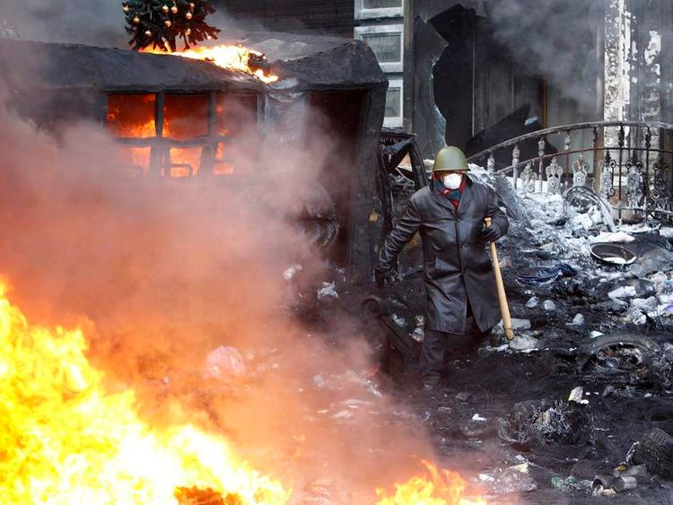 A pro-European integration protester walks at the site of clashes with riot police in Kiev