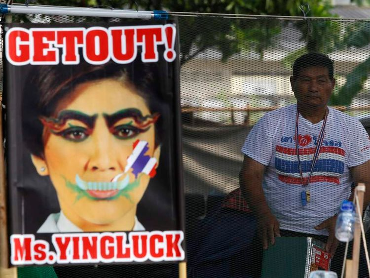 An anti-government protester stands next to a defaced image of Thailand's PM Yingluck during a rally in Bangkok