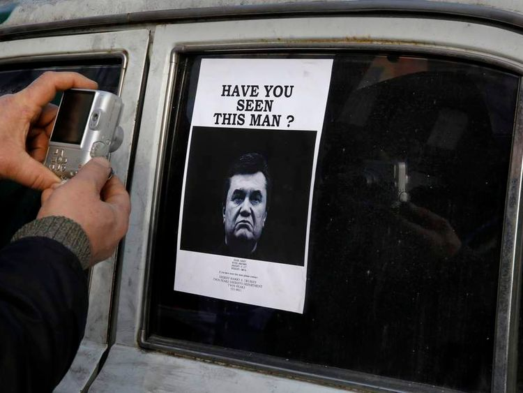 "A man takes photos of a ""Wanted"" notice for fugitive Ukrainian President Yanukovich near Kiev's Independent Square"