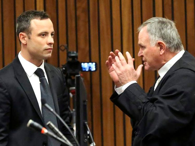Olympic and Paralympic track star Oscar Pistorius listens to his lawyer Barry Roux ahead of his trial for the murder of his girlfriend Reeva Steenkamp in Pretoria