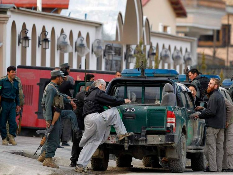 Afghan policeman evacuate foreigners from the site of an attack in Kabul