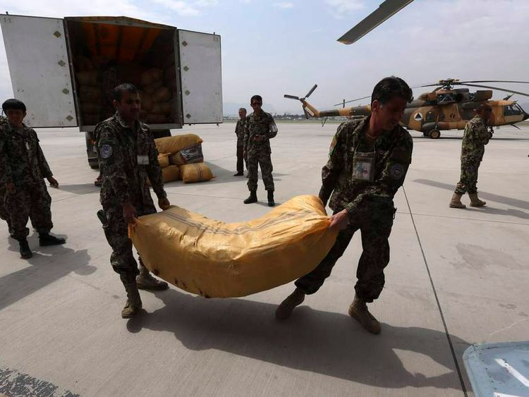 Afghan National Army troops load supplies for survivors of the Badakhshan landslide onto helicopter in Kabul.