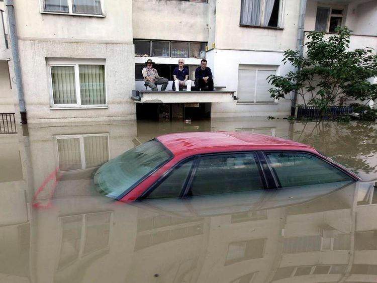 Men sit on a car porch during heavy floods in Bosanski Samac
