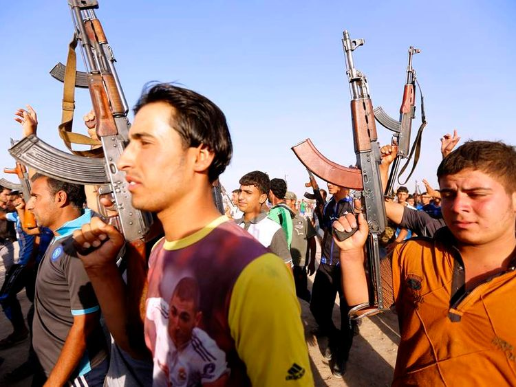 Volunteers, who have joined the Iraqi Army to fight against predominantly Sunni militants from the radical Islamic State of Iraq and the Levant, carry weapons during a parade in Al-Fdhiliya district