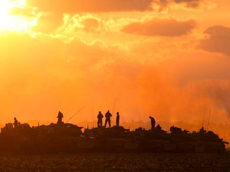 Israeli soldiers stand on top of their tanks and armoured personnel carriers across from the northern Gaza Strip.