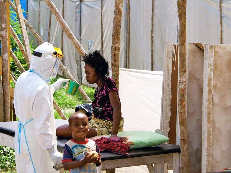 Handout of a health worker, wearing personal protection gear, offering water to a woman infected with Ebola virus desease at a treatment centre in Kenema Government Hospital in Kenema