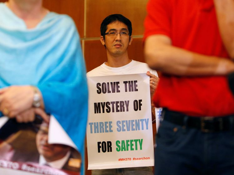 A family member of a passenger on the missing plane holds a placard pleading for continued searching