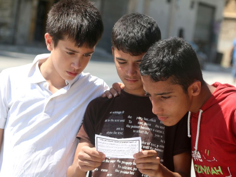 Boys read one of the leaflets dropped by the army over rebel-held districts