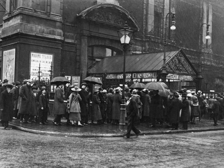 People queuing in the rain outside Madame Tussaud's Waxworks in London, around 1930.