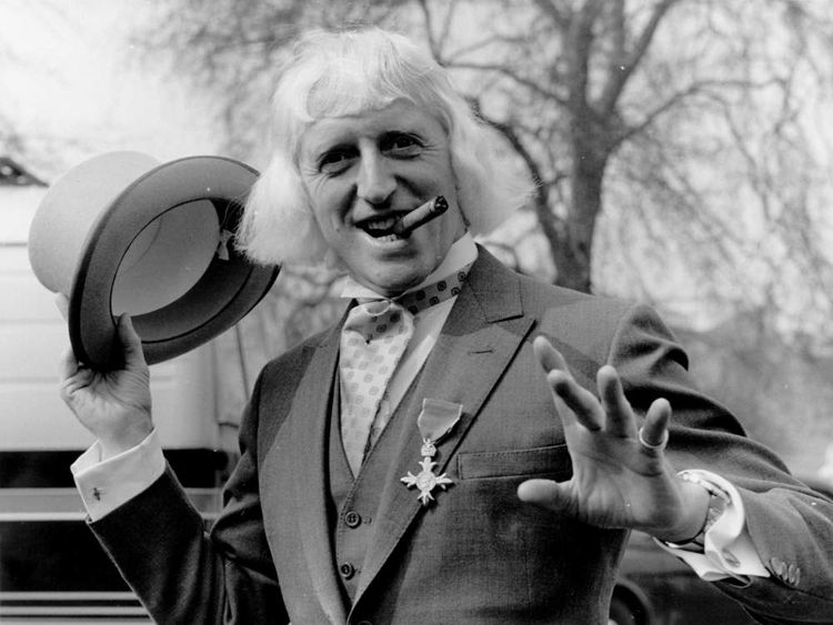 British radio disc jockey, television broadcaster and charity fundraiser Sir Jimmy Savile sporting his OBE