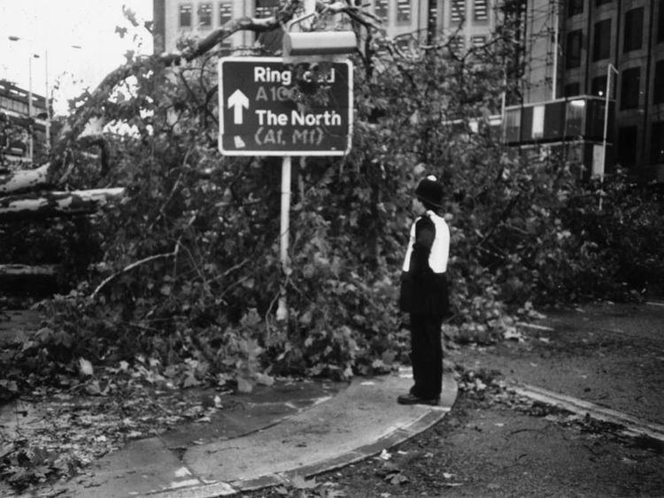 A policeman surveys the damage on a London road in 1987