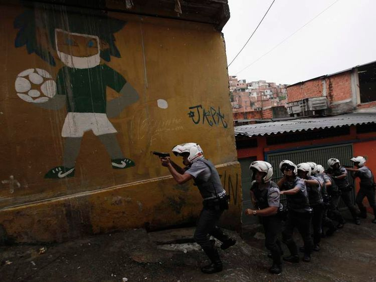 Police officers patrol next to wall graffiti of a football player