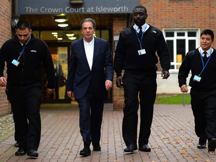 Security personnel escort British art tycoon Charles Saatchi (2nd L) as he leaves Isleworth Crown Court