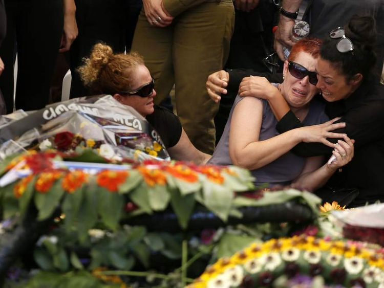 The mother (2nd from R) of 20-year-old Israeli St. Sgt. Amit Yeori mourns by his flower covered fresh grave during the funeral at the Mount Herzl military cemetery in Jerusalem,
