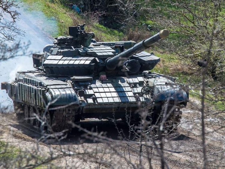A Russian tank rolls outside a former Ukrainian military base in Perevalnoye, near the Crimean capital Simferopol