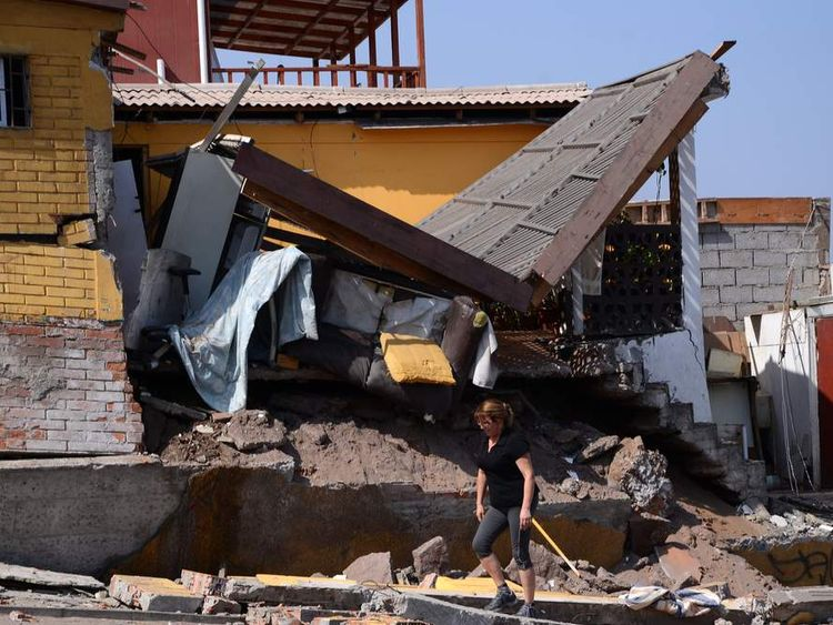 A woman walks next to a destroyed house in Iquique, northern Chile, after a powerful earthquake