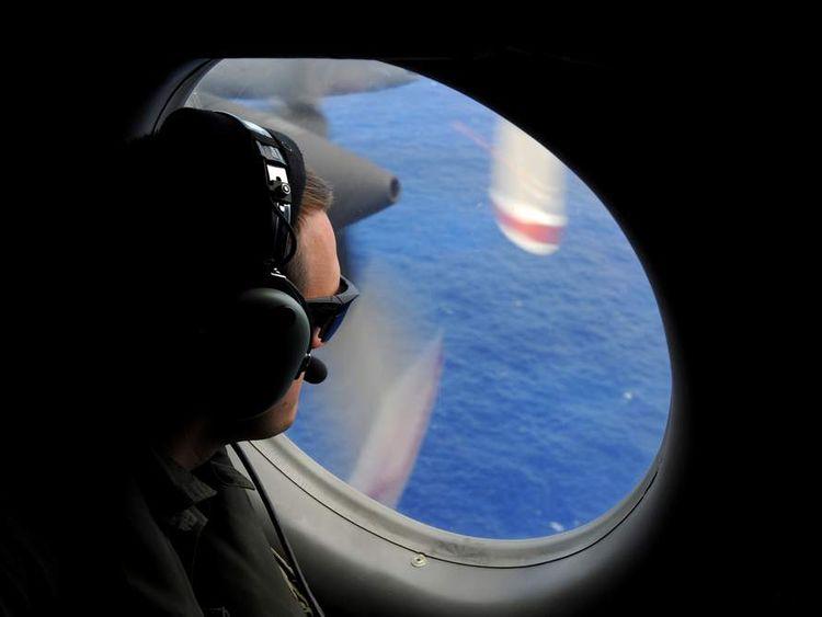 A crew member of a Royal New Zealand Airforce P-3K2-Orion aircraft helps to look for objects during the search for missing Malaysia Airlines flight MH370
