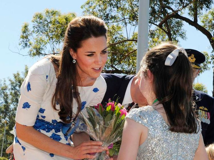Kate accepting some flowers from a little girl