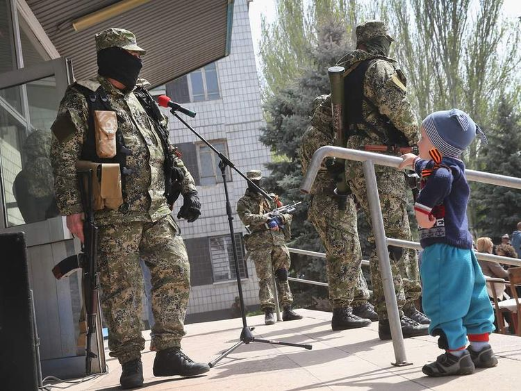 A child looks at pro-Russian militants guarding the front of the city council building on April 28, 2014 in Konstantinovka, Ukraine.