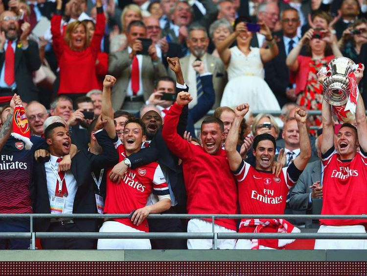 Captain Thomas Vermaelen of Arsenal (R) lifts the trophy in celebration after the FA Cup with Budweiser Final match between Arsenal and Hull City at Wembley Stadium.