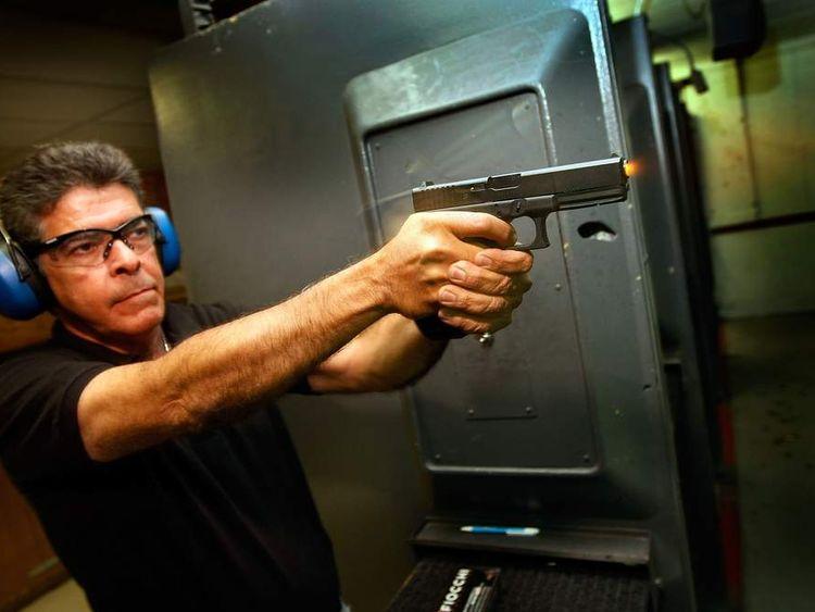 Luiz Santos fires his 40mm pistol at the Pembroke Gun & Range shop in Florida