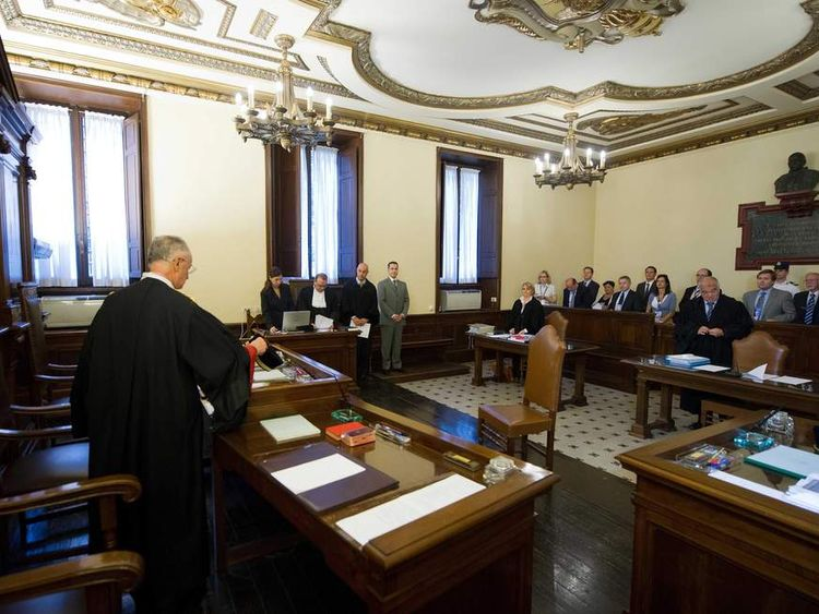 In this photo released by the Vatican paper L'Osservatore Romano, the Pope's butler Paolo Gabriele, fifth from left, in grey suit, stands in the wood-trimmed courtroom of the Vatican tribunal, at the Vatican,