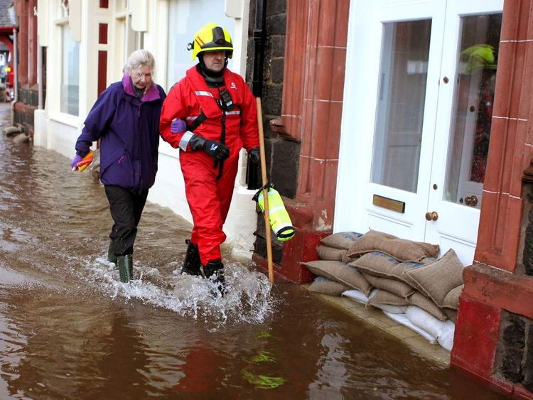 A fireman helps a member of the public through Aberfoyle