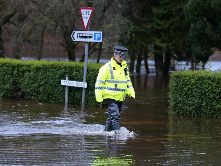 A police man walks through Aberfoyle which has been flooded after the River Forth burst its banks.