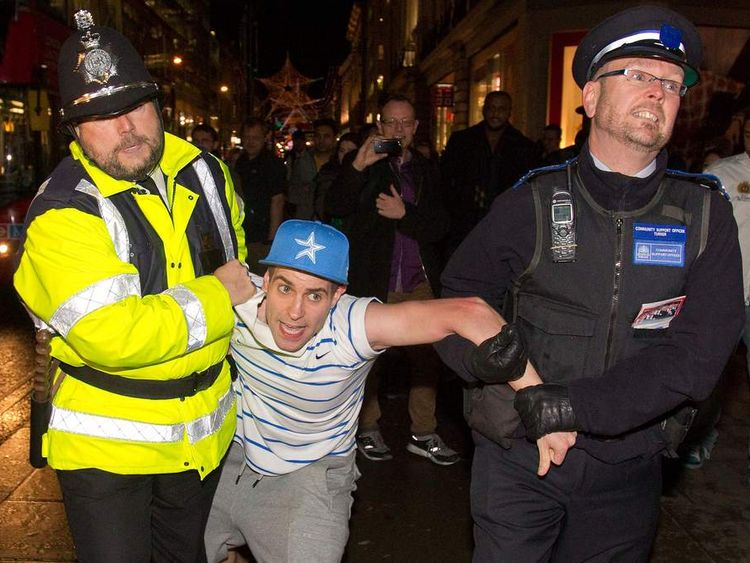 Lee Nelson is restrained by an actor playing a policeman (left) and a real Community Support Officer after a PR stunt