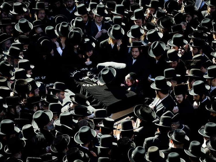 Members of the Orthodox Jewish community grieve at the funeral of two expectant parents
