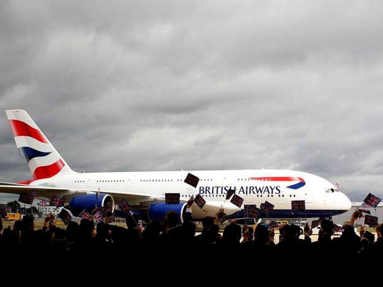 British Airways staff look at a British Airways Airbus A380.
