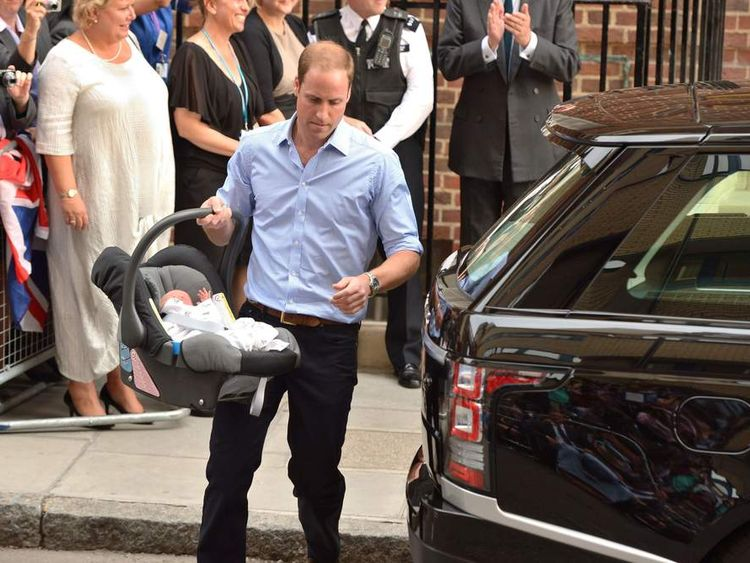 The Duke of Cambridge carries his new son to the car