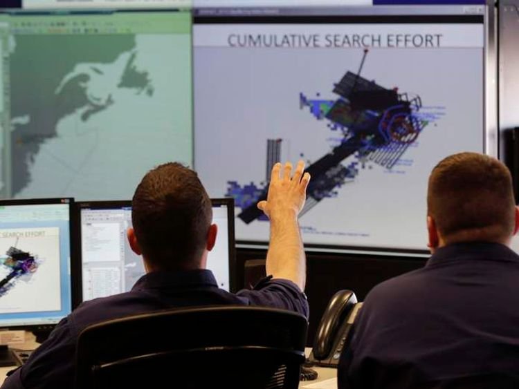 Operations unit controllers check search pattern maps while trying to find a missing yacht.