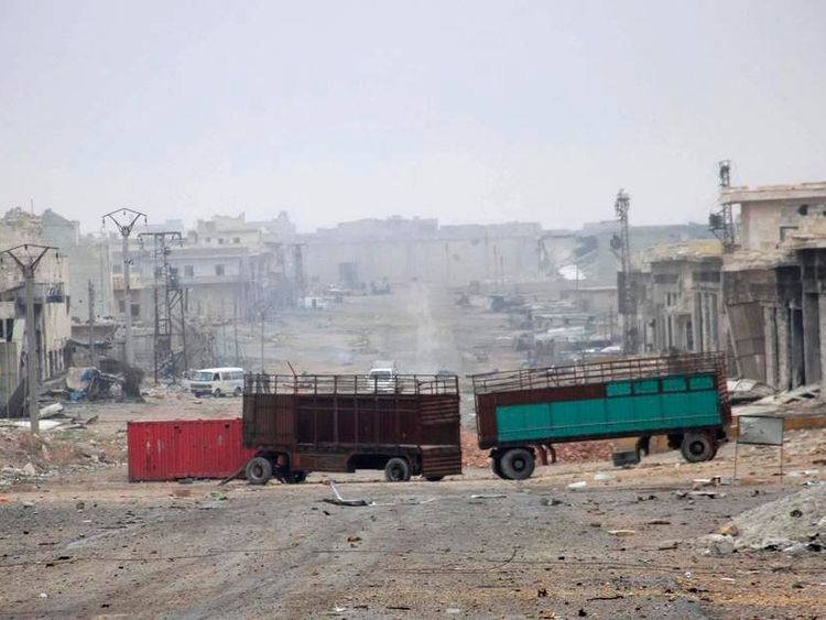 Damaged buildings and vehicles are pictured along deserted street in Aleppo town of Naqaren