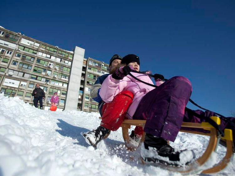 Children play with a snow sledge in Zagreb