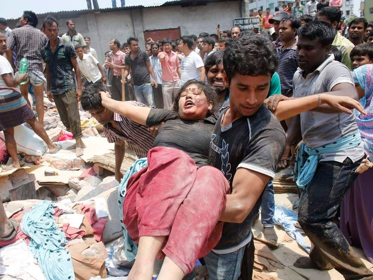 People rescue a garment worker, who was trapped under the collapsed Rana Plaza building in Savar