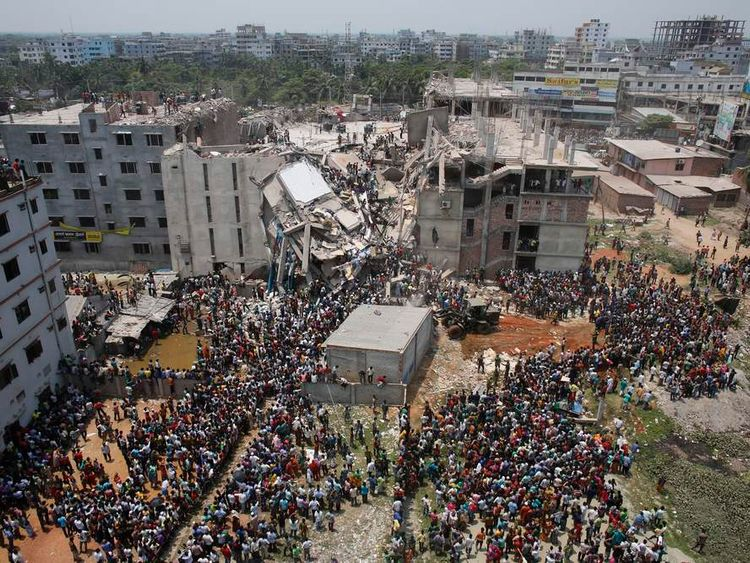Crowds gather at the collapsed Rana Plaza building as people rescue garment workers trapped in the rubble, in Savar