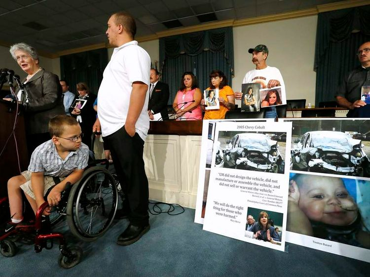 Buzard looks at a picture of himself as a toddler when he was paralyzed in a GM car crash at a news conference on Capitol Hill