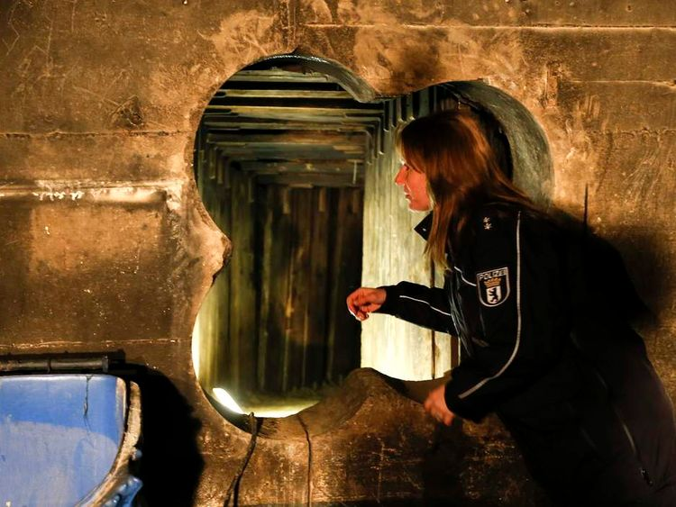 A police officer looks through entrance of a tunnel dug by thieves in order to enter the safe deposit room of a bank in Berlin