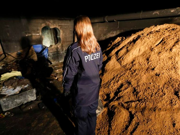 Police officer stands next to entrance of a tunnel dug by thieves leading to the safe deposit room of a bank in Berlin