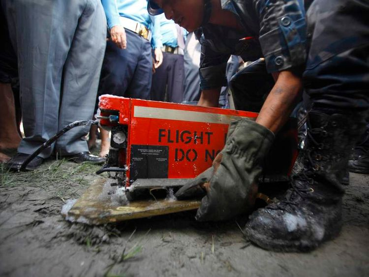 A Nepalese police officer carries a black box from the crash site