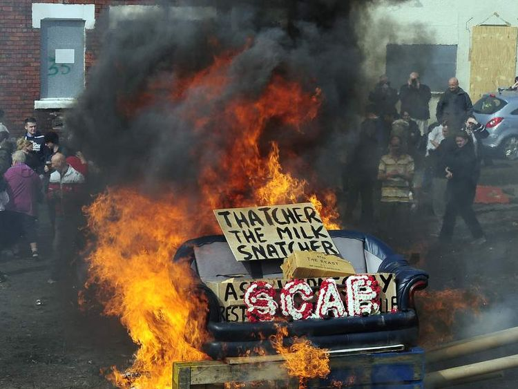 Protesters set fire to a coffin containing an effigy of Margaret Thatcher after a protest march