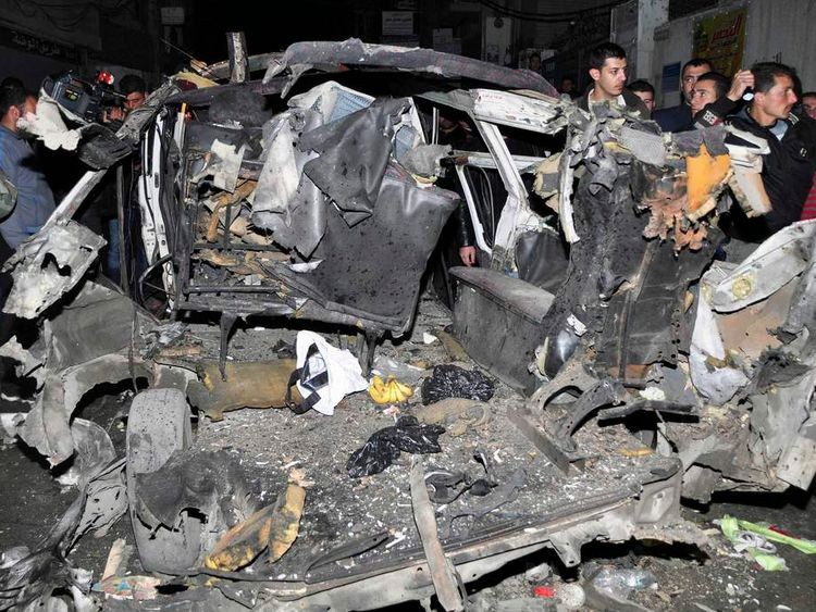 SANA photo shows a crowd gathering around wrecked vehicles after a bomb explosion in a minibus at the Mazeh 86 area in Damascus