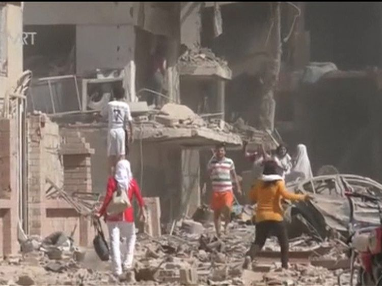 Searching through rubble after bombing in Qamishli, Syria