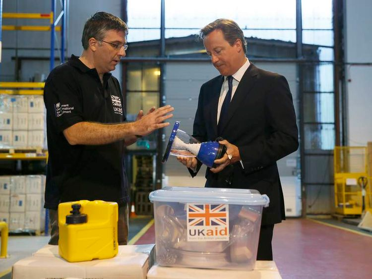 David Cameron talks to Julian Neale as he visits a UK aid Disaster Response Centre at Kemble Airport