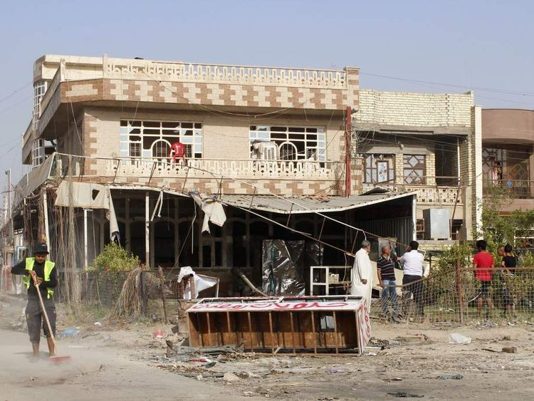 A worker cleans up the site of a car bomb attack in Baghdad